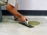 Repairing the cored holes in the concrete slab floor with fresh concrete and cleaning up the Pasadena home.
